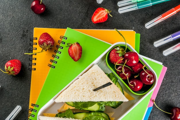 Back to school. a hearty healthy school lunch in a box: sandwiches with vegetables and cheese, berries and fruits (apples) with notebooks, colored pens on a black table.
