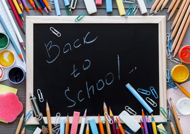 Back to school inscription written on chalkboard with kids supplies for modern primary education, color pencils, paints and other multicolored accessories on grey wooden desk, top view from above