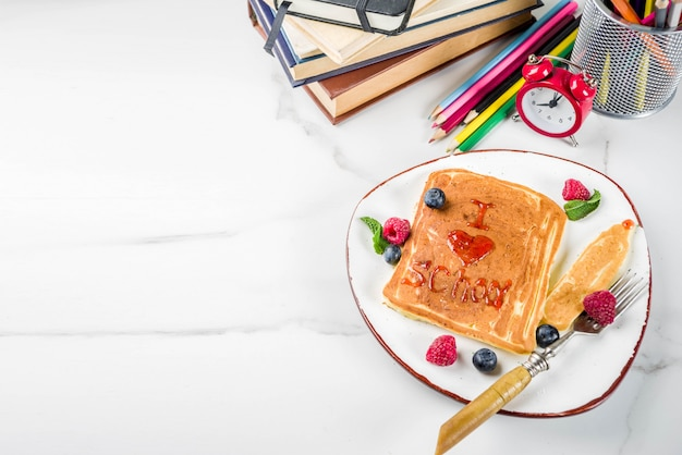 Back to school kids breakfast concept, pancakes with raspberry jam - i love school, on white marble stole, with books, alarm clock, pencils, school supplies. top view