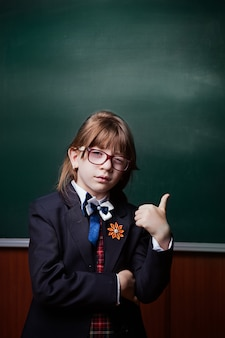 Back to school. love to learning. thumb up. the girl in uniform and glasses smiles, gestures to the side