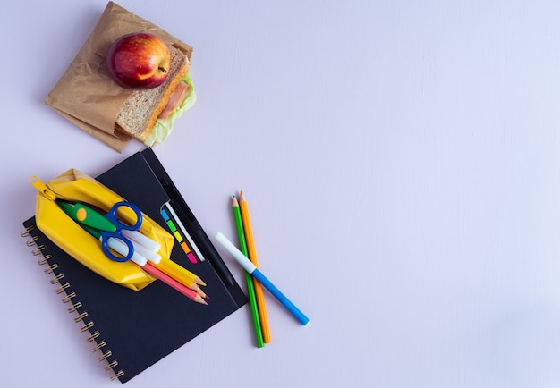 Back to school material. pencils, notebook and sandwich on purple background. copy space.