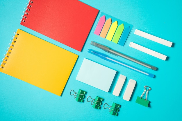 Back to school mock up. flat lay composition with notebook, sticker, binder, pen, chalk, pencil. isometric concept on blue background. pop art. school supplies. overhead. branding mock up stationery
