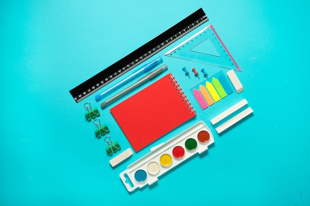 Back to school mock up. flat lay composition with a watercolor, pencil, notebooke, ruler, eraser. isometric concept on blue background. pop art. school supplies. overhead. branding mock up stationery