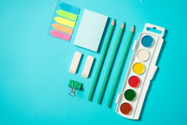 Back to school mock up. flat lay composition with a watercolor, pencil, sticker, eraser. isometric concept on blue background. pop art. school supplies. overhead. branding mock up stationery