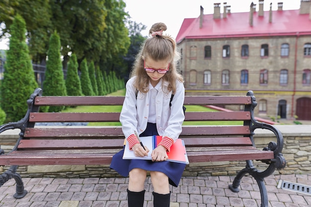 Back to school. outdoor portrait of beautiful blond girl 9, 10 years old with backpack writing in notebook