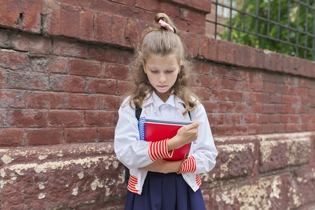 Back to school. outdoor portrait of beautiful blond girl near brick wall of fence school building