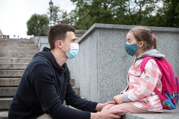 Ritorno a scuola, pandemia. giovane padre e piccola figlia in una maschera. rapporti familiari amichevoli.