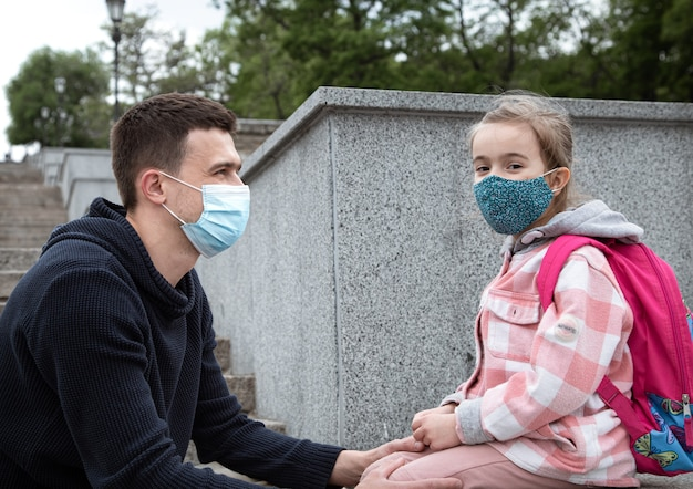 Back to school, pandemic. young father and little daughter in a mask. friendly family relationships.