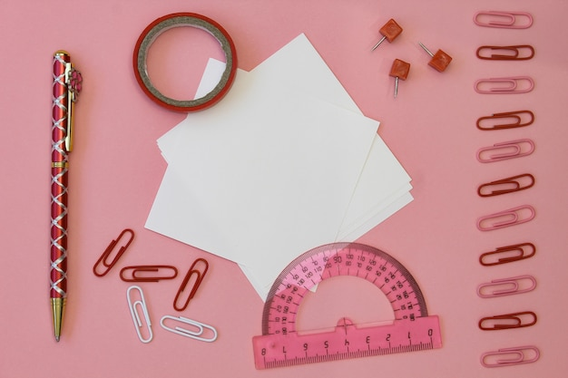 Back to school . paper for writing with pencils, clips and tape on a pink background.