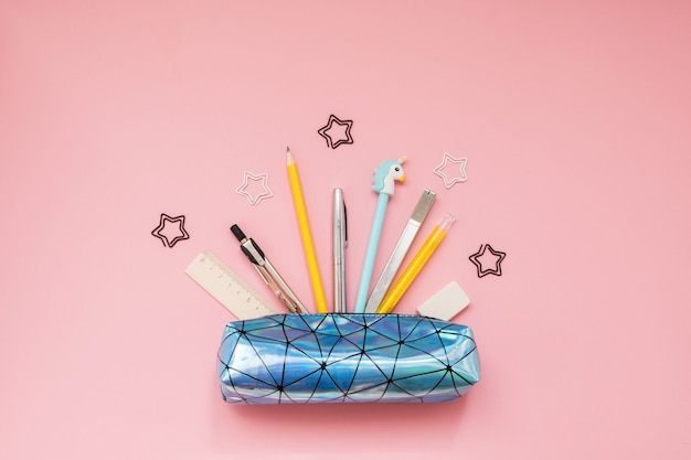 Back to school. pencil case with school supplies on pink table