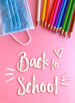Back to school, pencils and mask in pink background