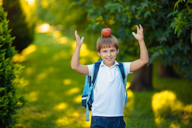 Back to school. portrait of happy smiling child boy with apple on head in park