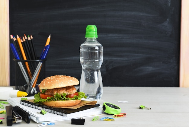 Back to school. quarantine education. lunch box with hamburger, water and school accessories on the background of the school board.
