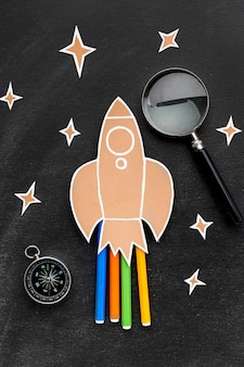 Back to school rocket with magnifying glass and pencils