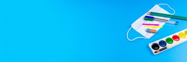 Back to school. school accessories on a blue background. photo banner, top view, space for text.