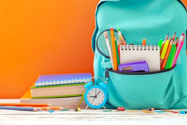 Back to school. school backpack with different supplies and alarm clock on orange background