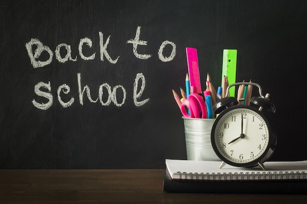 Back to school. school supplies, copybook and pen. copy space on chalkboard.