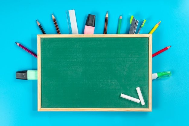 Back to school . school supplies and green blackboard on blue
