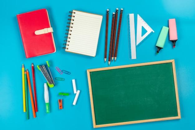 Back to school . school supplies and green blackboard on blue