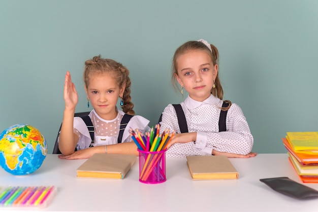 Back to school schoolgirls write draw in a notebook sitting at the table and do homework