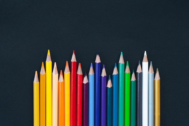 Back to school shot of color pencil pile pencil nibs on black background