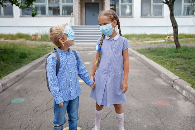 Back to school siblings with backpacks in medical masks stay near doors before first offline day