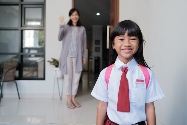 Back to school. smiling asian pupil girl with backpack going to school. indonesian student uniform Premium Photo
