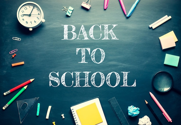 Back to school and  stationary supplies on blackboard background.top view design