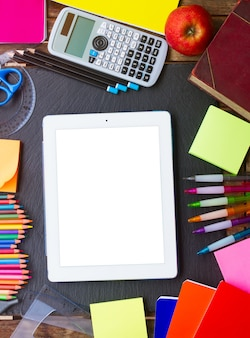 Back to school supplies as a frame of tablet on blackboard, top view