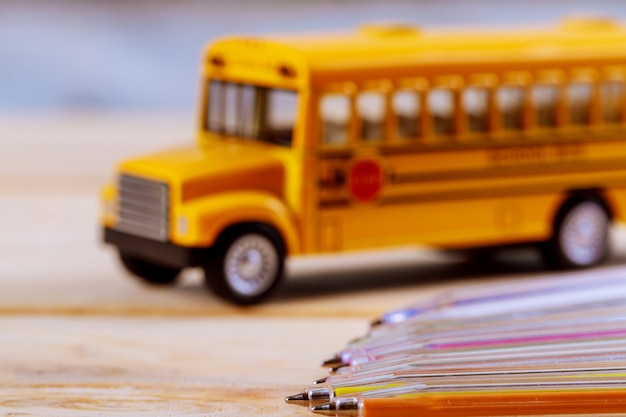 Back to school supplies colored pencils toy yellow school bus on wooden background