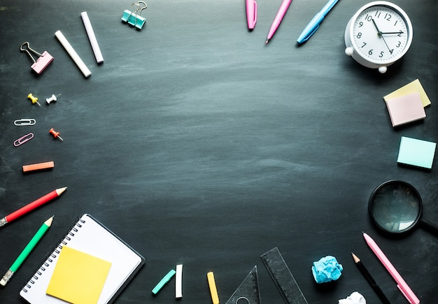 Back to school supplies and office accessories on blackboard background.top view design