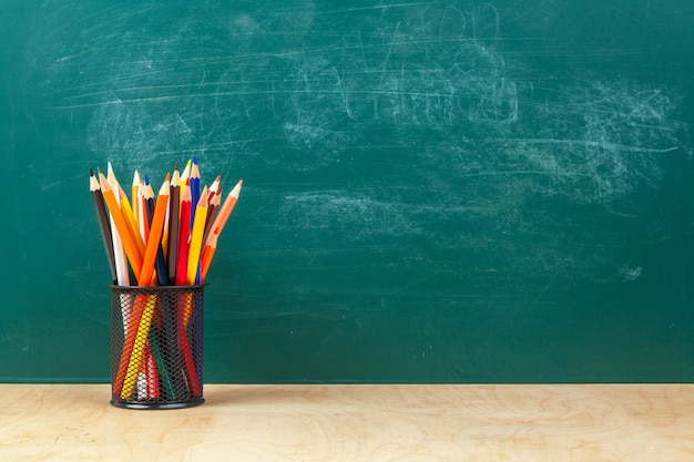 Back to school template design, with school supplies and greenboard background Premium Photo