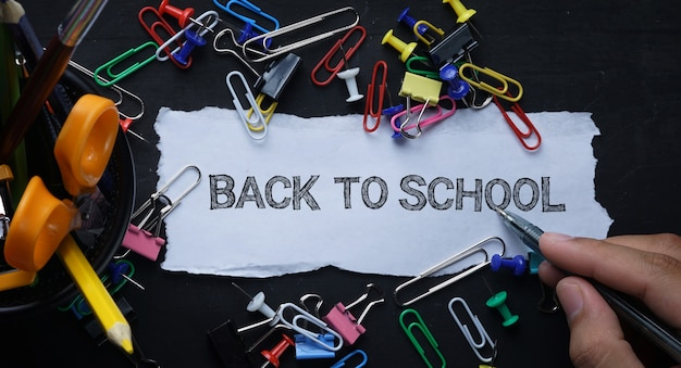Back to school tex. torn paper and school stationary on blackboard