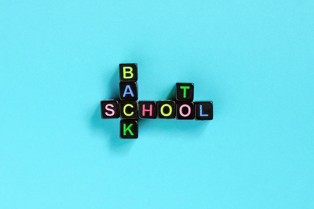 Back to school text from colorful letters on black cubes laid out in form of crossword puzzle