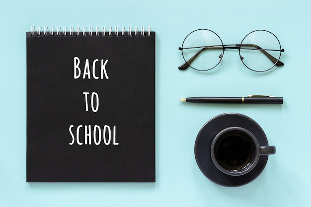 Back to school text and office supplies, stationery. black color notepad, cup of coffee, spectacles and pen on blue background.