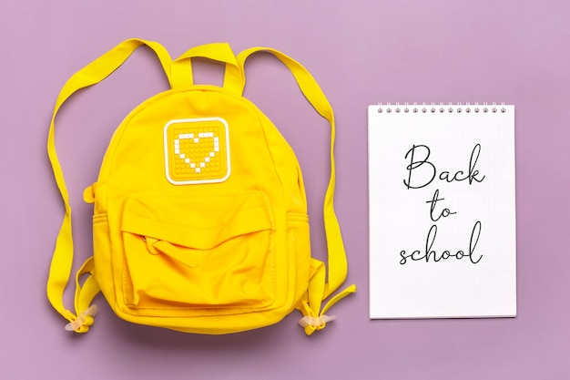 Back to school text on open notepad, education concept. yellow backpack isolated on violent background. top view flat lay composition student accessory