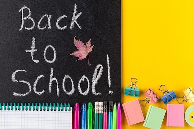 Back to school text, school stationary and blackboard.