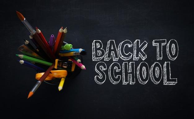 Back to school text. school stationary on blackboard