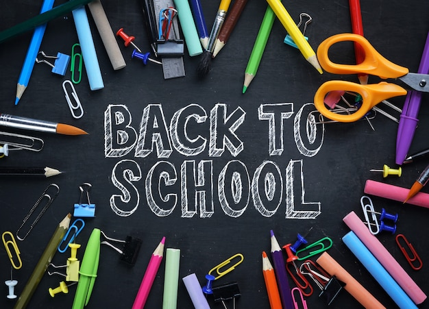 Back to school text. school stationary top view on blackboard