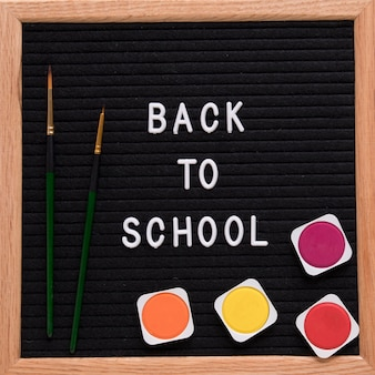 Back to school text on slate with colorful watercolor paints and paintbrush