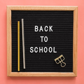 Back to school text on slate with pencils and bulldog clip on colorful backdrop