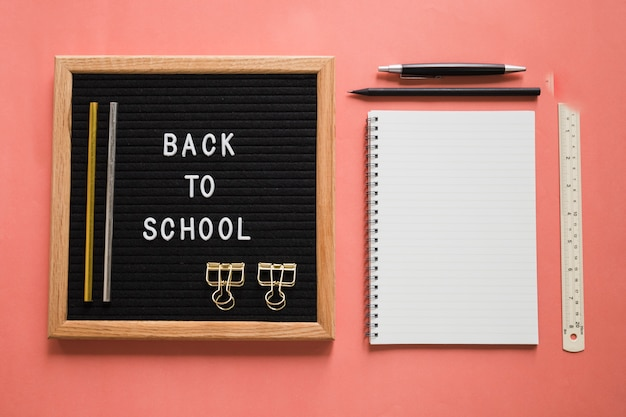 Back to school text on slate with stationeries on colorful background