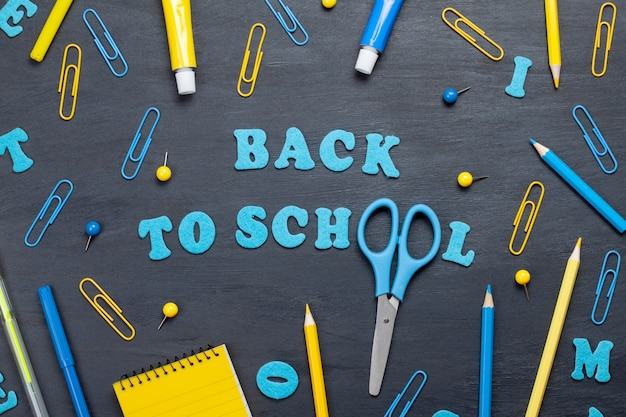 Back to school text with colorful stationary over the blackboard