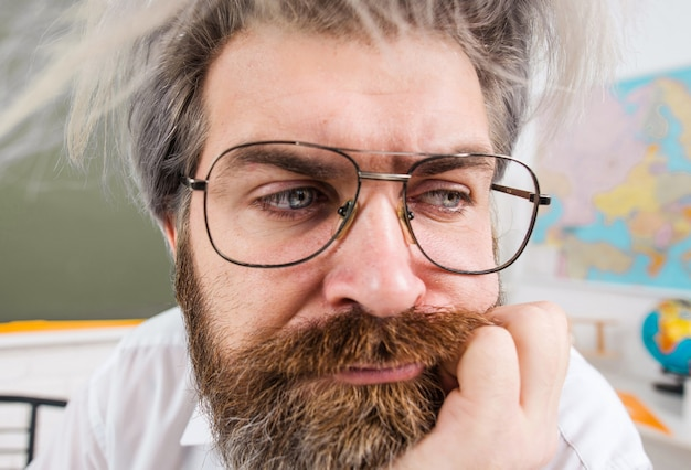 Back to school. thoughtful male teacher in glasses in classroom. closeup portrait. school advertising.
