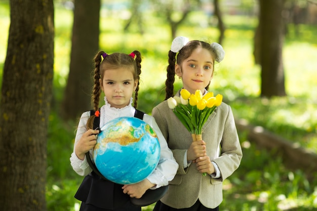 Back to school. two cheerful caucasian girls schoolgirls with flowers and a globe
