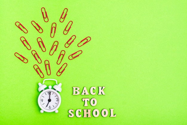 Back to school. white alarm clock rings and the text in wooden letters on a green background