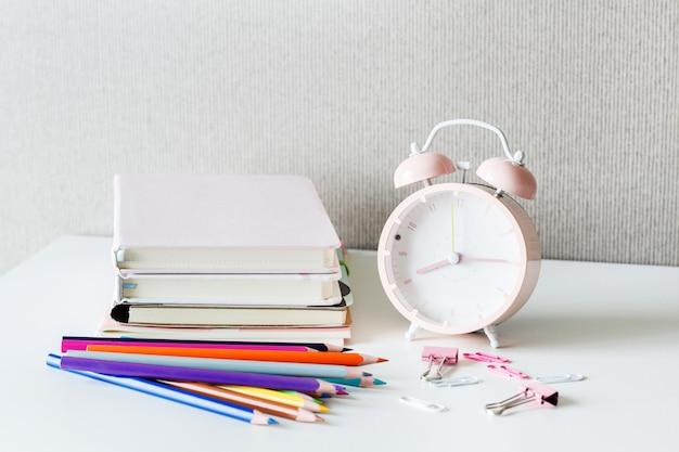 Back to school on white table. books, pencils, alarm clock on desk.