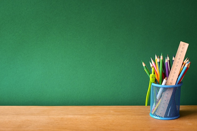 Back to school with blue glass with school supplies on a school desk on a background of a clean green chalk board