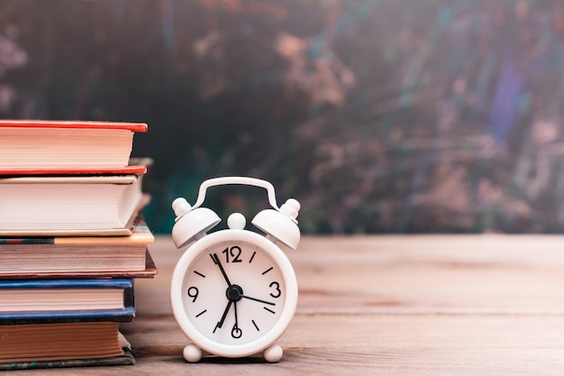 Back to school with books and clock on a wooden table over blackboard
