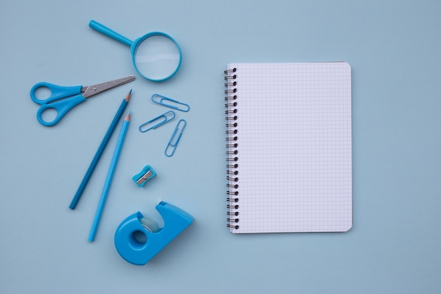 Back to school with empty notebook for mock up scissors, magnifying glass  on light blue